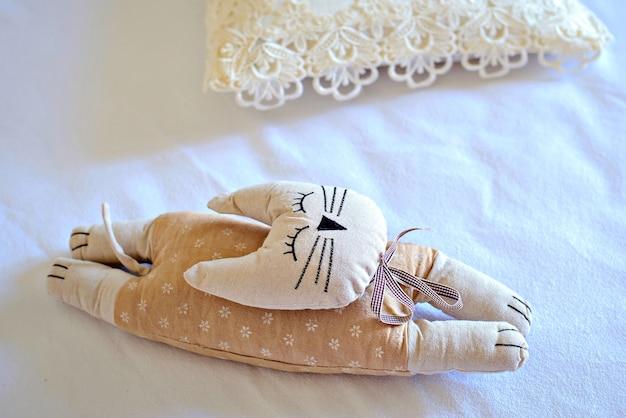 ぼろきれのおもちゃの猫がベッドに横たわっています