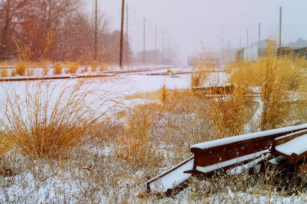 철도는 태양이 비추는 거리로 들어갑니다. 철도는 눈으로 덮여 있습니다.