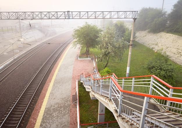 レールは霞に溶け、rightob鉄道駅の人けのないプラットフォーム