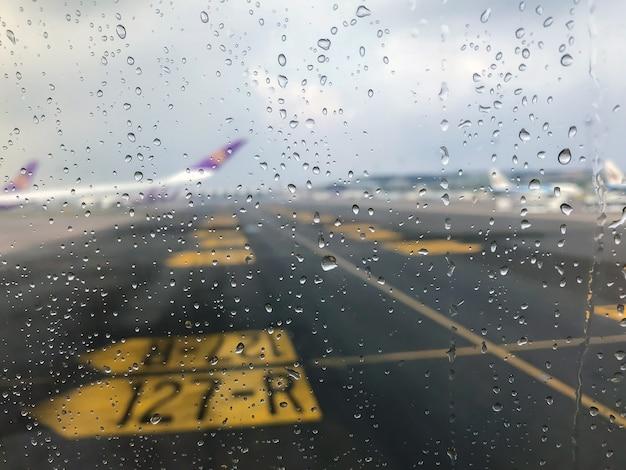 滑走路に駐車している旅客機の窓の外のガラスに雨が降る。