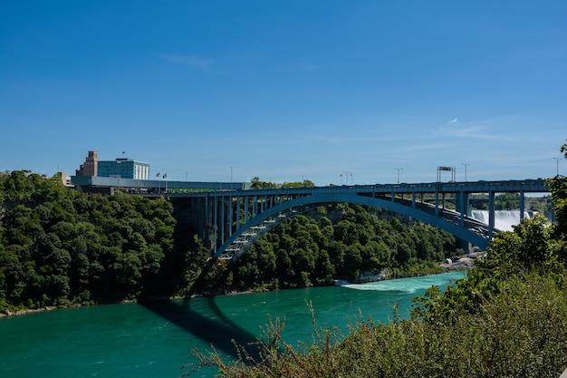Радужный мост пересекает реку ниагара и является пограничным переходом, соединяющим ниагарский водопад онтарио, канада, с ниагарским водопадом в нью-йорке, сша.