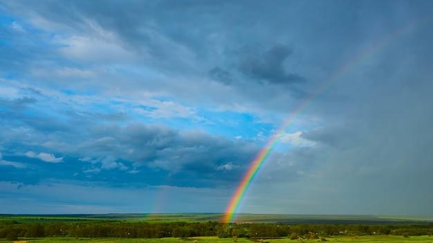 雷雨の後の田園風景の上の虹。