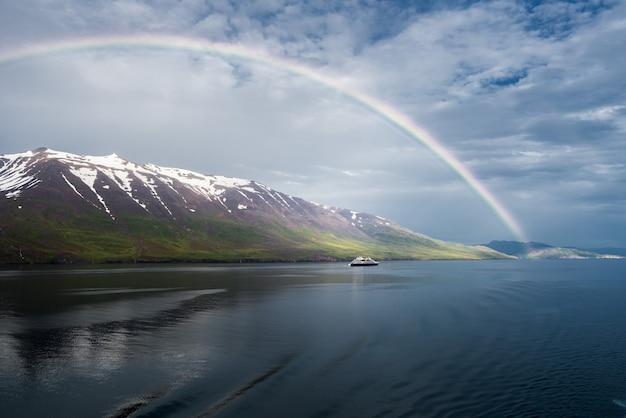 雪に覆われた山々と孤立した船の近くの海にかかる虹