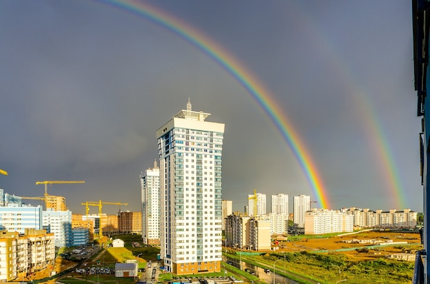虹は街の高層ビルに広がっています。
