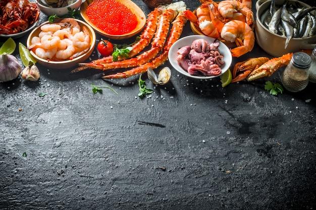 В ассортименте разные морепродукты. на черном деревенском