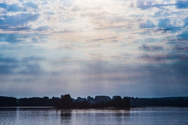 강 풍경에서 신의 광선 태양 광선은 물 복사 공간에 구름을 통해 빛난다
