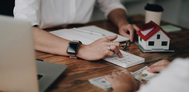 不動産業者は、クライアントが家の保証金を支払った後、家の契約を作成します。話し合い、交渉、取引の成立