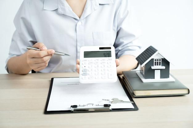 Агент по недвижимости объясняет покупателю-женщине договор о ведении бизнеса, аренду или страхование жилья.