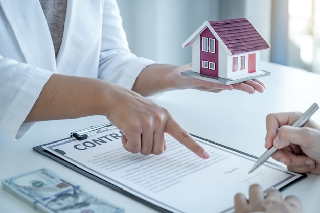 Агент по недвижимости показывает рукой и объясняет покупателю деловой договор, аренду, покупку, ипотеку, ссуду или страхование жилья.