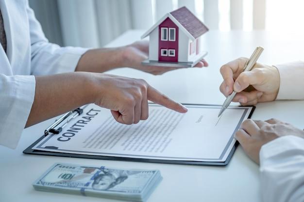 Агент по недвижимости указывает рукой и объясняет деловой договор покупателю-мужчине.