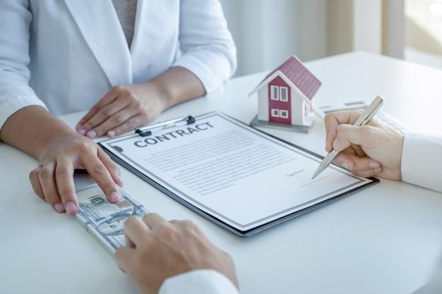 Агент по недвижимости передает деньги и объясняет деловой договор покупателю.
