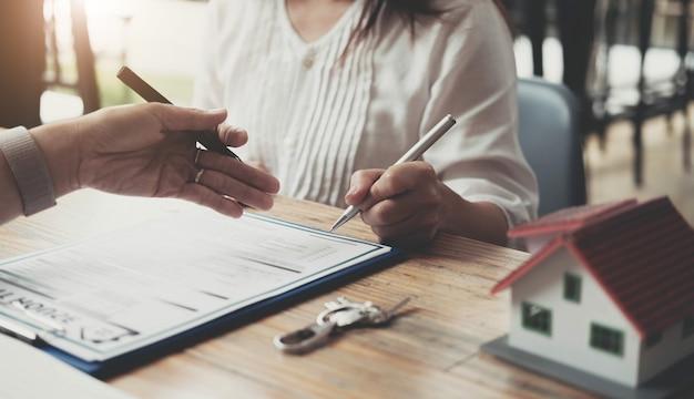 부동산 중개인은 주택 설계 및 구매 계약, 모기지 대출 승인 주택 대출 및 보험 개념을 보기 위해 연락하는 고객에게 주택 스타일을 설명하고 있습니다.