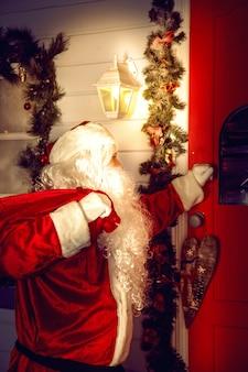 진짜 산타 클로스. 산타가 문을 두드립니다. 크리스마스 밤
