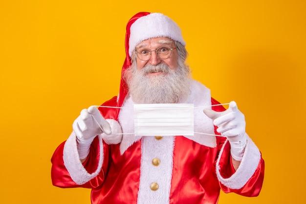노란색 배경을 가진 진짜 산타클로스, 보호 마스크, 안경, 모자를 들고 있습니다. 사회적 거리두기가 있는 크리스마스. 코로나 19