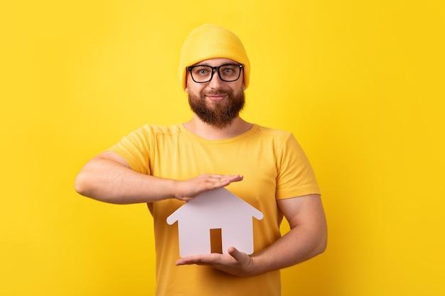 노란색 배경 위에 집을 들고 있는 부동산 중개인, 집을 사고 팔거나 임대하는 개념