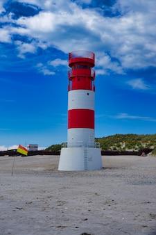 푸른 하늘이있는 섬 모래 언덕-heligoland-독일의 빨간색과 흰색 작은 등대