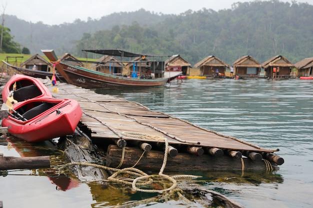 Красная каноэ и остановка лодки возле хижины сено на плоту в чеоу лан дам винтаж от отдыха