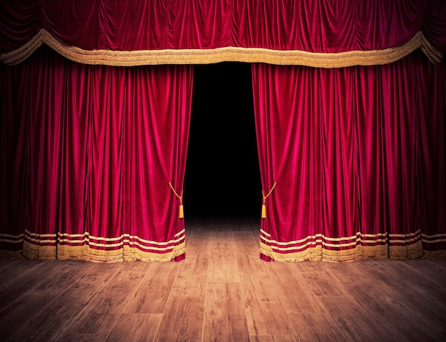 Красные занавески сцены открываются перед театральным представлением.