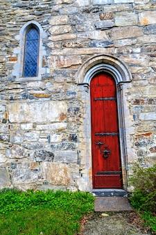 中世の石造りの教会への赤い扉