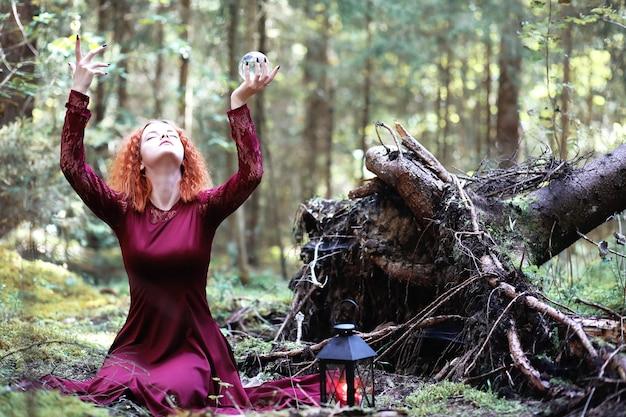 Рыжая ведьма проводит ритуал с хрустальным шаром в лесу