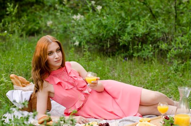 オレンジジュースのグラスとピンクのドレスで赤い髪の女性。