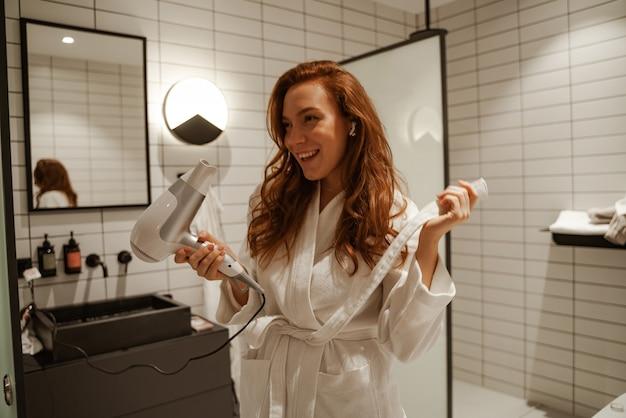 赤毛の若い女性はシャワーで楽しんでいます、彼女は彼女の手でヘアドライヤーを持っています。