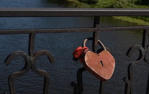 Замок в форме красного сердца на ограде моста concept padlocks love forever