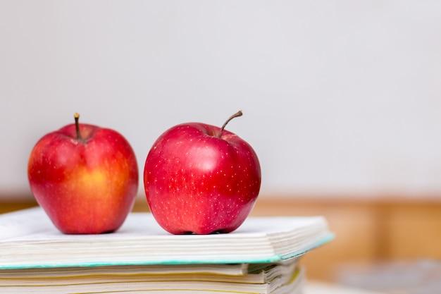 赤いジューシーなりんごは開いた本の上に横たわる