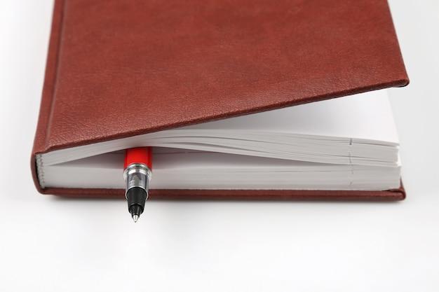 Красная ручка находится внутри блокнота