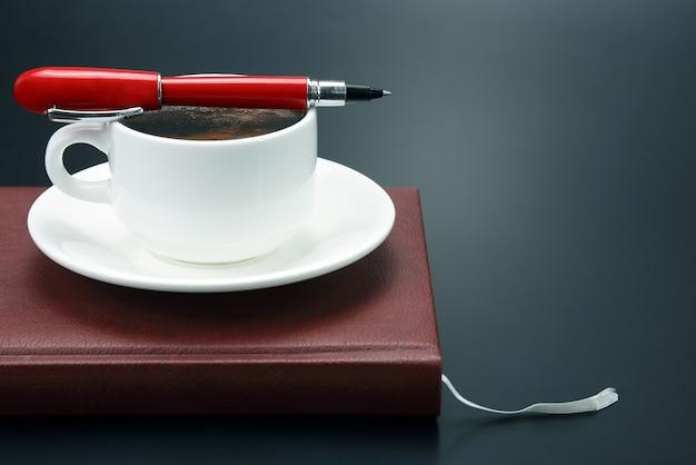 빨간 펜은 블랙 커피와 노트북과 함께 컵에 있습니다.
