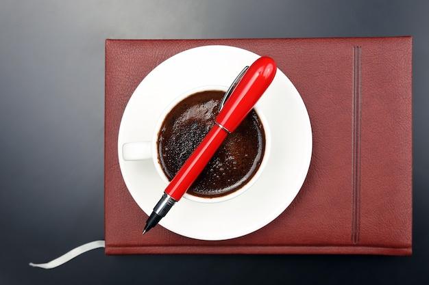 Красная ручка находится на чашке с черным кофе и блокноте.