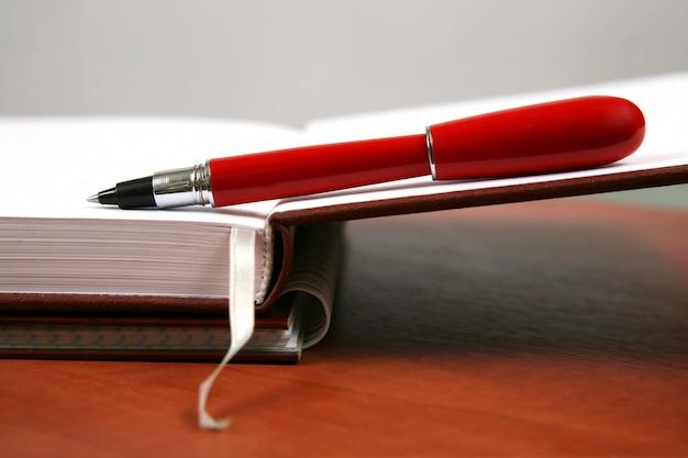 열린 노트북에 누워있는 빨간 펜