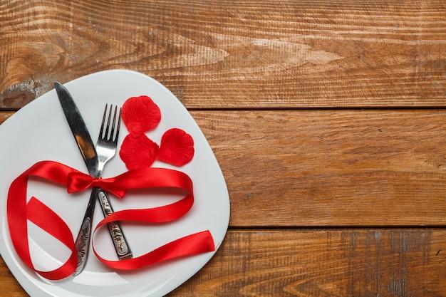 木製の背景のプレートに赤いリボン。バレンタインデーのコンセプトです。