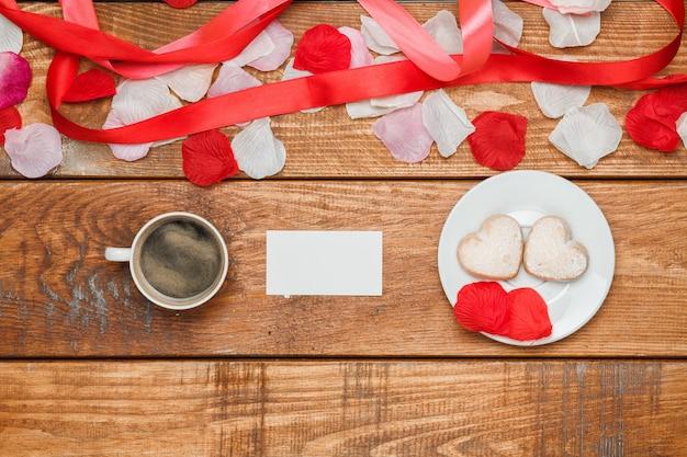 Красная лента, маленькие сердечки на деревянном с чашкой кофе