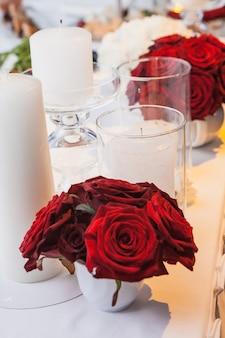 お祝いのテーブルの上の赤いバラとキャンドル