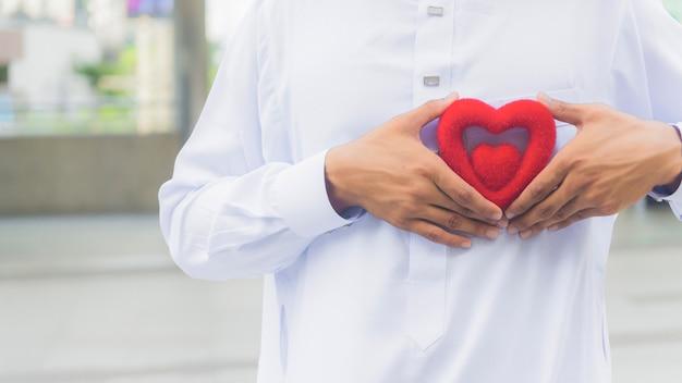 Сердце красного символа на руке священника или руки человека