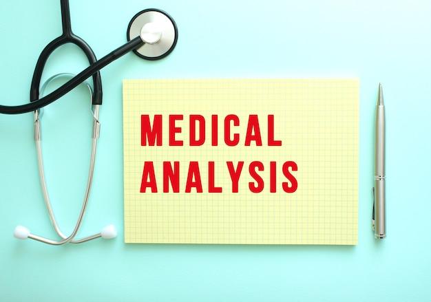 빨간색 텍스트 medical analysis는 파란색 배경의 청진기 옆에 있는 노란색 패드에 작성됩니다.