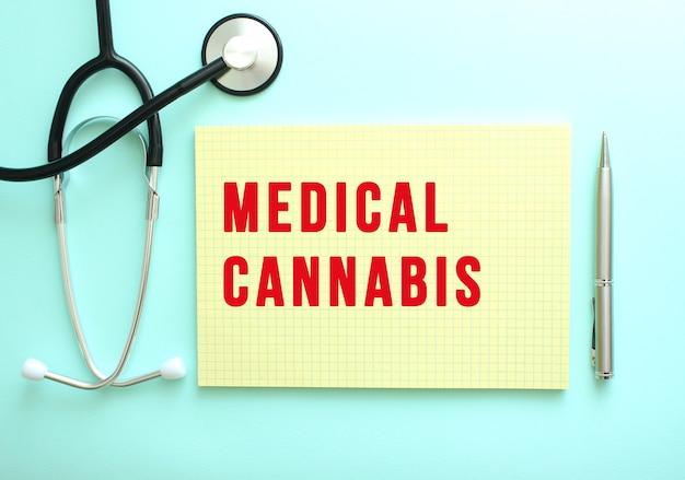 빨간색 텍스트 medical cannabis는 파란색 배경의 청진기 옆에 있는 노란색 패드에 쓰여 있습니다. 의료 개념