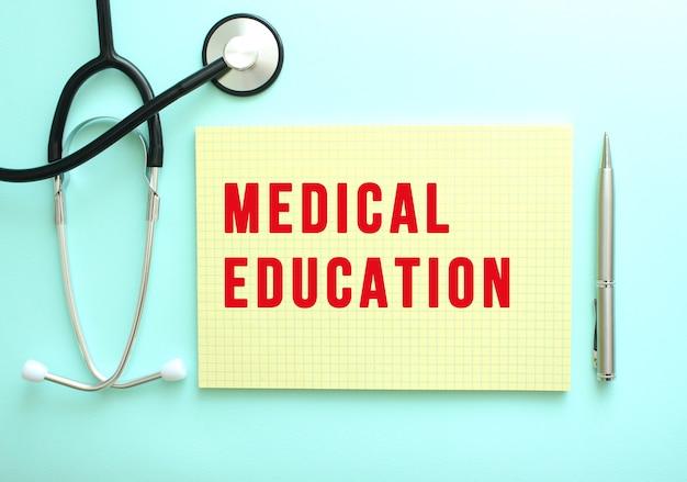 빨간색 텍스트 medical education은 파란색 배경의 청진기 옆에 있는 노란색 패드에 쓰여 있습니다. 의료 개념