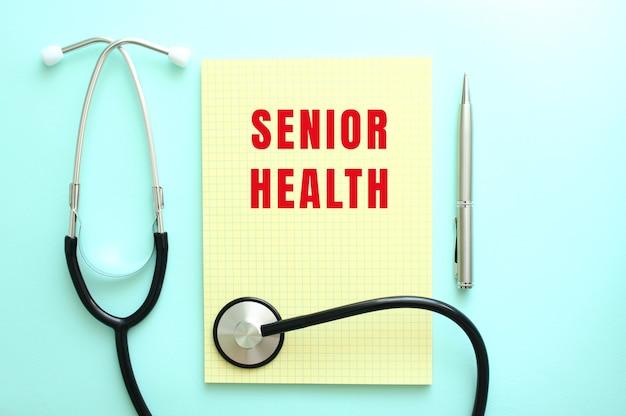 빨간색 텍스트 senior health는 파란색 배경의 청진기 옆에 있는 노란색 패드에 쓰여 있습니다. 의료 개념