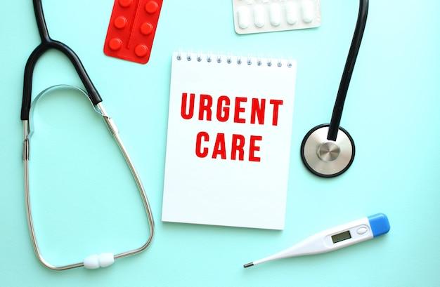 파란색 배경에 청진기 옆에 있는 흰색 메모장에 빨간색 텍스트 urgent care가 쓰여 있습니다.