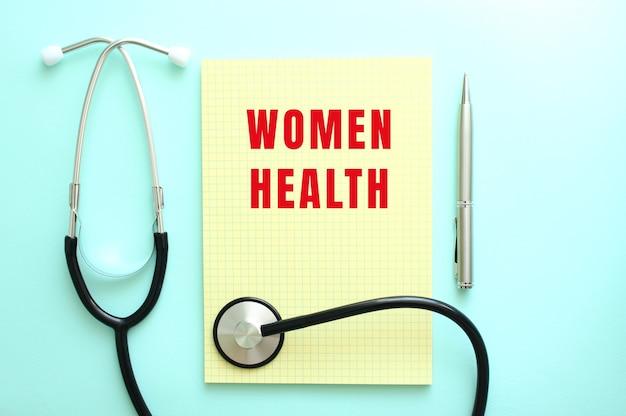 빨간색 텍스트 women health는 파란색 배경의 청진기 옆에 있는 노란색 패드에 쓰여 있습니다. 의료 개념