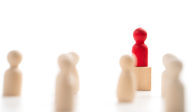箱の上に立っている赤い木製の人物は、影響力とエンパワーメントを示しています。リーダーチーム、成功した競争の勝者、影響力のあるリーダーのためのビジネスリーダーシップの概念