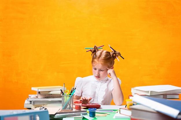 집에서 책을 많이 가진 빨강 머리 십 대 소녀. 스튜디오 촬영