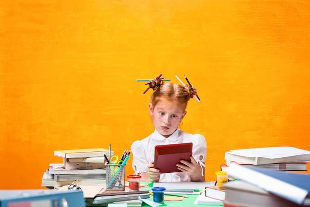 Рыжая девушка с большим количеством книг в домашних условиях. студийный снимок