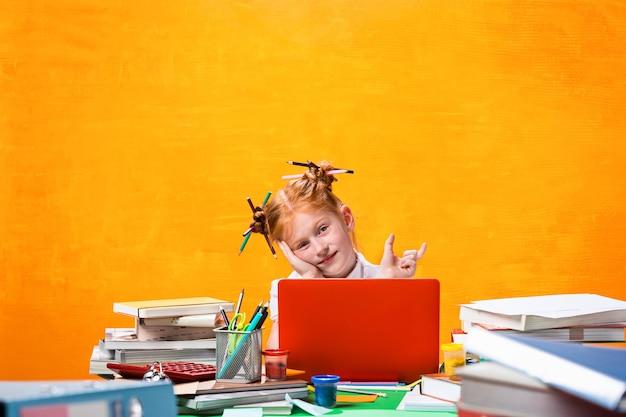 Рыжая девочка-подросток с множеством книг дома. студийный снимок