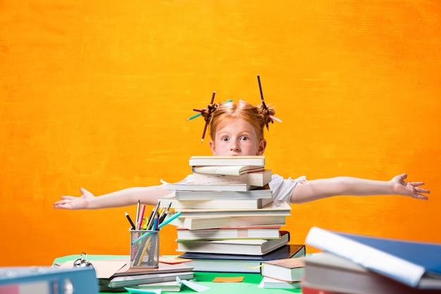 Рыжая девушка с большим количеством книг в домашних условиях.
