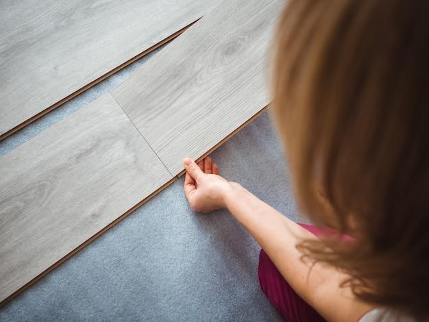 Процесс ремонта в квартире. девушка кладет ламинат на пол. вид сзади