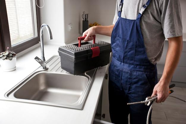 修理人はキッチンのいくつかの問題を修正するようになりました