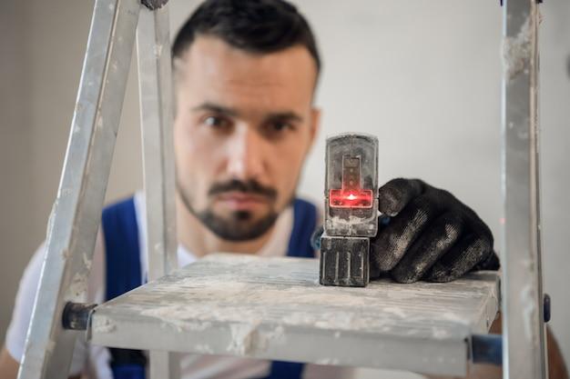 Мастер в перчатках и спецодежде наносит разметку с помощью нивелирного инструмента.